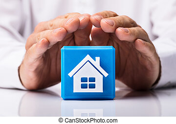Human Hand Protecting Cubic Block With Home Icon