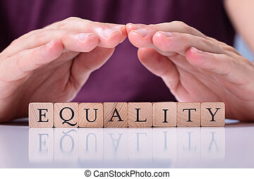 Human Hand Protecting Equality Word On Wooden Blocks