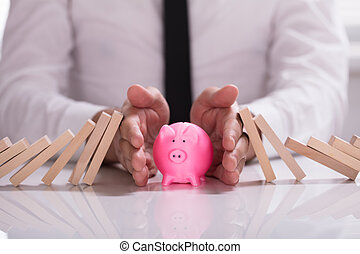 Human Hand Protecting Piggybank From Falling Wooden Blocks