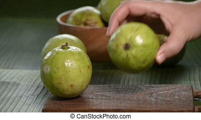 human hand put guava on cutting board