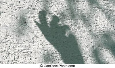 human hand shadow on white wall background.