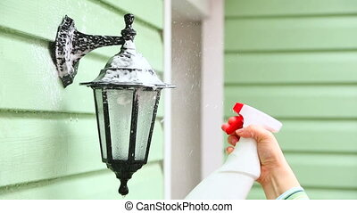 Human Hand Spraying Detergent Onto Street Lamp