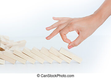 Human hand starting a domino effect concept with wooden...