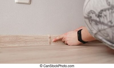 Human hand touches the plastic baseboard with a screwdriver ...