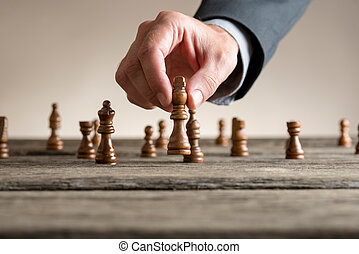Human hand wearing business suit moving dark King chess piece