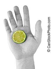 human hand with a green lemon