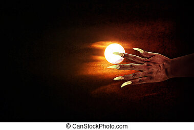 Human hand with long fingernail or devil hand on full moon...