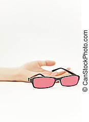 Human hand with pink glasses