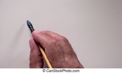 """Human hand writing word """"HELLO"""" in french with blue gouache"""