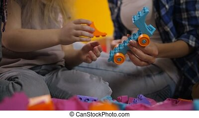 Human hands creating toys from constructor blocks