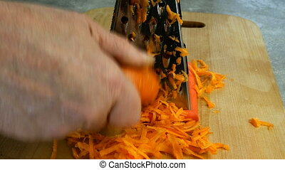 Human hands grate raw carrot on a metal grater on wooden cutting board for making soup or salad. Rubbing carrot. Cooking vegetarian healthy food. Close-up. Homemade food.