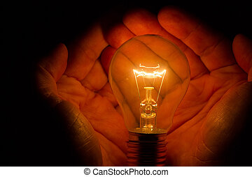 Human hands holding a light bulb to conserve energy darkness