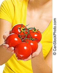 Human hands holding fresh ripe tomatoes