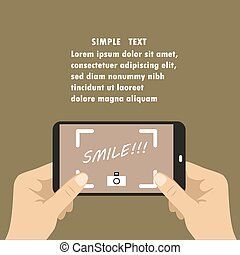 Human hands holding mobile phone camera with Smile! text on screen
