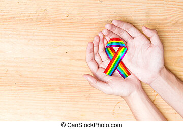 Human hands holding ribbon with rainbow flag