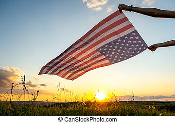 Human hands holding waving american national flag in field at sunset.