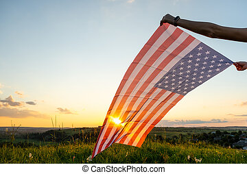 Human hands holding waving USA national flag in field at sunset.