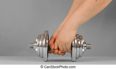 Human hands lift heavy metal dumbbell on a green background. Sports, home fitness, weight loss.