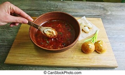 human hands mix traditional borscht and sour cream with ...