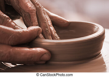 human hands moulding with the clay on a potter`s wheel close up.