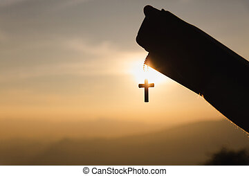 human hands praying to the GOD while holding a crucifix symbol with bright sunbeam.