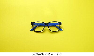 Human hands search, find and take eye glasses in blue plastic frame. On yellow background. Close-up.