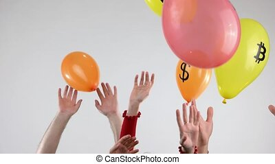 Human hands throw up balloons with symbols of cryptocurrency. People and air balloons with various cryptocurrency images.