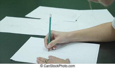 Human hands with pencil draw dress on paper on white table...