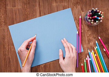 Human hands with pencil drawing something on the blue paper on wooden table