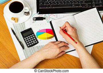 Human hands with pencil, notebook, keyboard, calculator, coffee on desktop.