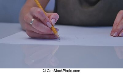 Human hands with pencil writing on paper on white table background