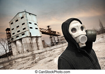 Human in gas mask outdoors and industrial factory on a...