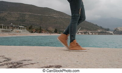 Human in ripped jeans and orange sneakers is on the sand coast.