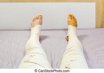 Human legs completely tight wrapped with woven elastic medical bandages and fixed with clips after surgery, outstretched on the bed. View in selective focus