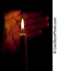 Human palm and a candle in the dark