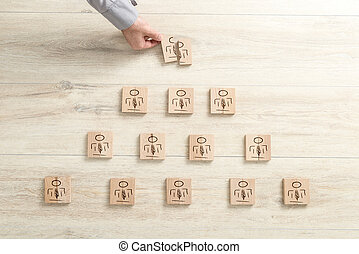 Human resources concept with pyramid of figures on wooden blocks