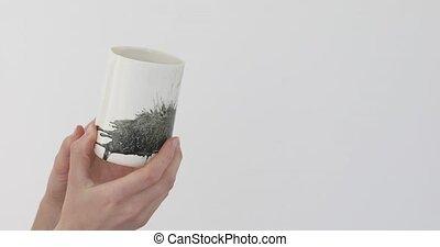Human shows beautiful mug - Hands twist stylish white mug...
