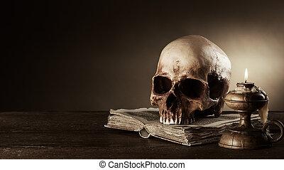 Human skull and ancient book still life