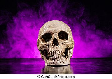Old human skull head with smoke on dark background