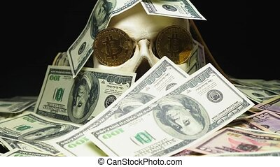 human skull in a pile of American currency. bitcoins in the...