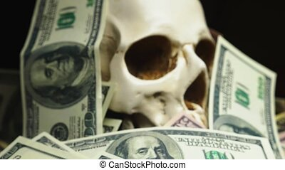 human skull in a pile of American currency on black...