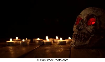 Human skull with flashing red eyes next to candles on a wooden table