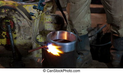 Human warms up the mold of metal by burner - Human warms up...