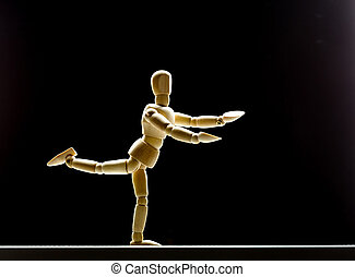 Human wood manikin is dancing on black