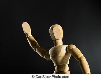 Human wood manikin waving closeup