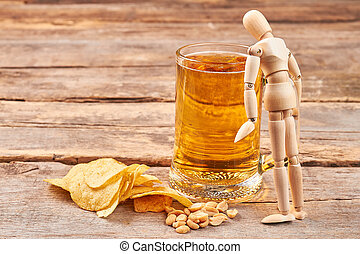 Human wooden dummy and glass of beer.
