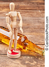 Human wooden dummy, bottle of alcohol.