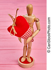 Human wooden dummy holding heart.