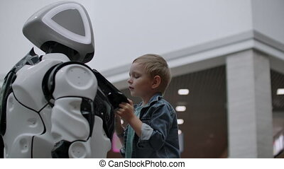 Humanoid robot talks with child at technology exhibition....