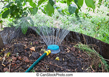 Humidification compost pile using sprinkler